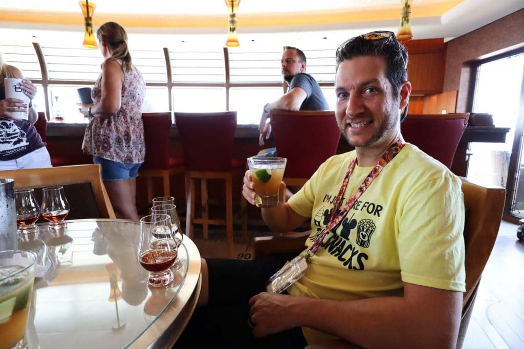 A man holding a drink at a beverage seminar on a Disney cruise.