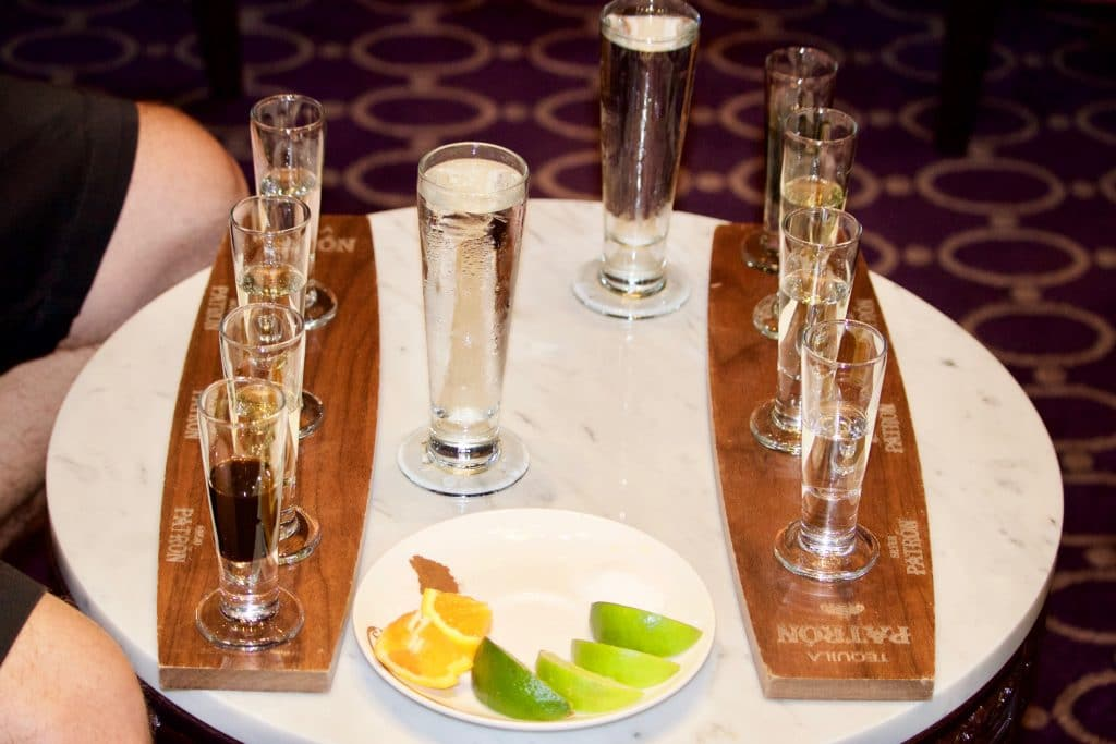 Tequila tasting trays on a white table with a plate of fresh limes on the Disney Fantasy.