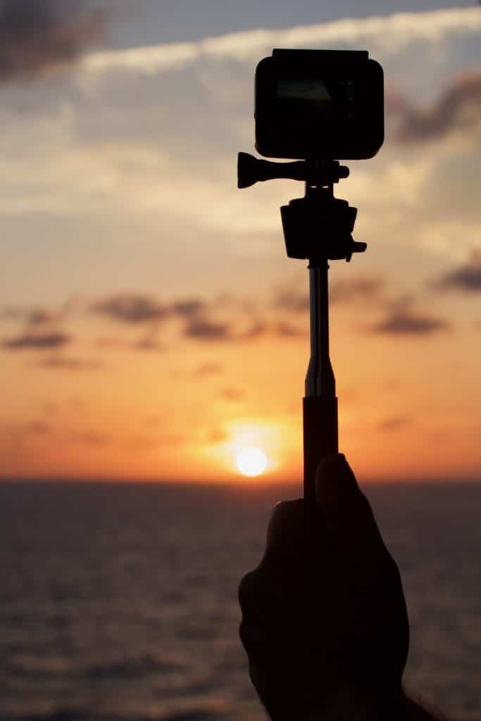 A hand holding a GoPro camera in front of a sunset on the water.