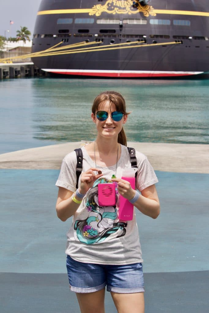 A woman is standing in front of the Disney Fantasy holding a pink water bottle and fan.