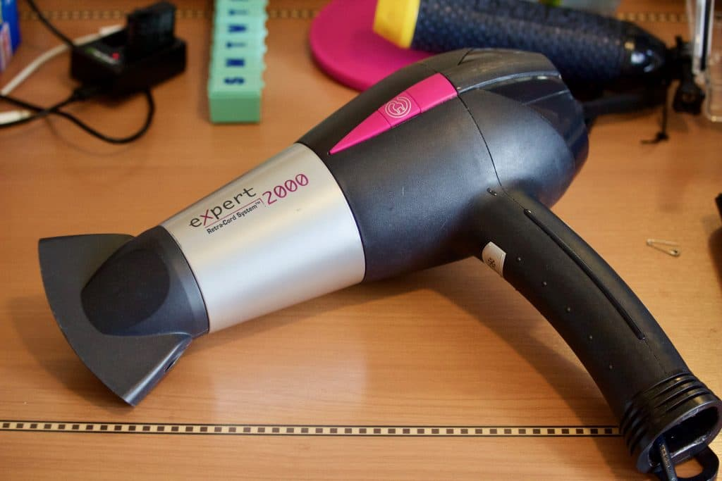 A hair dryer laying on a desk on a Disney cruise.