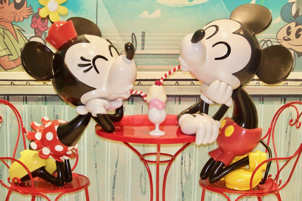 Mickey and Minnie sharing ice cream at a red table at Sweet on You on Disney Fantasy.