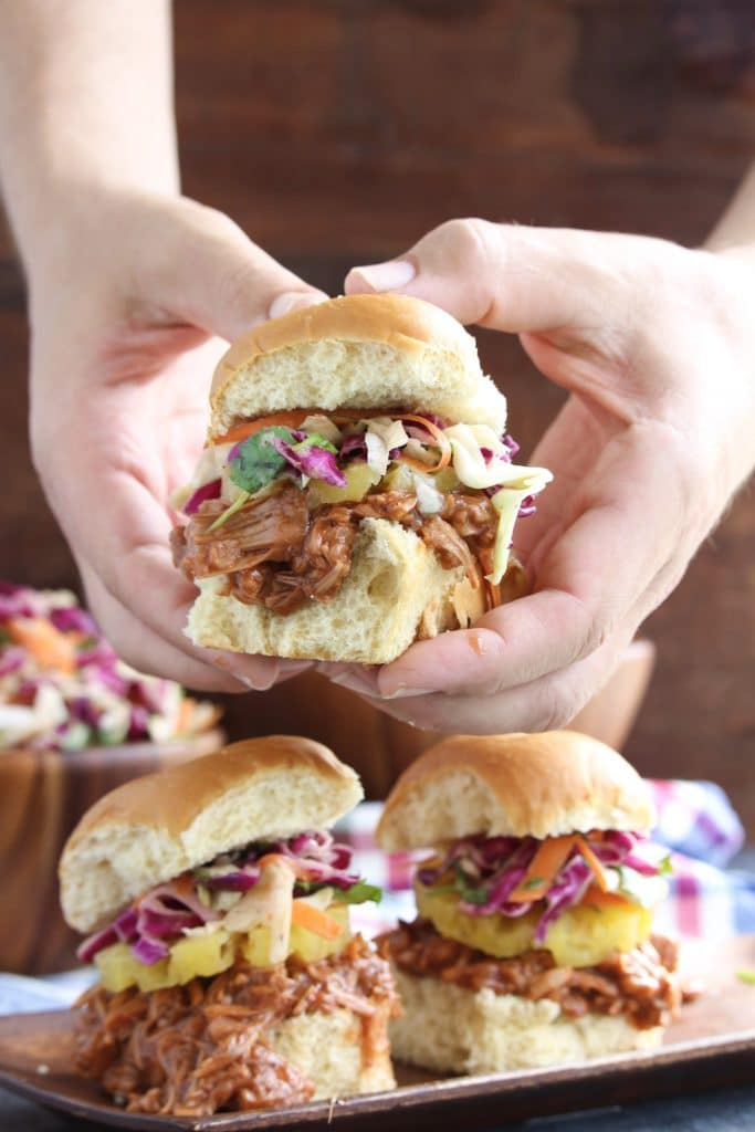 Two hands holding a vegan pulled pork slider over a tray of more sliders on a rustic background.