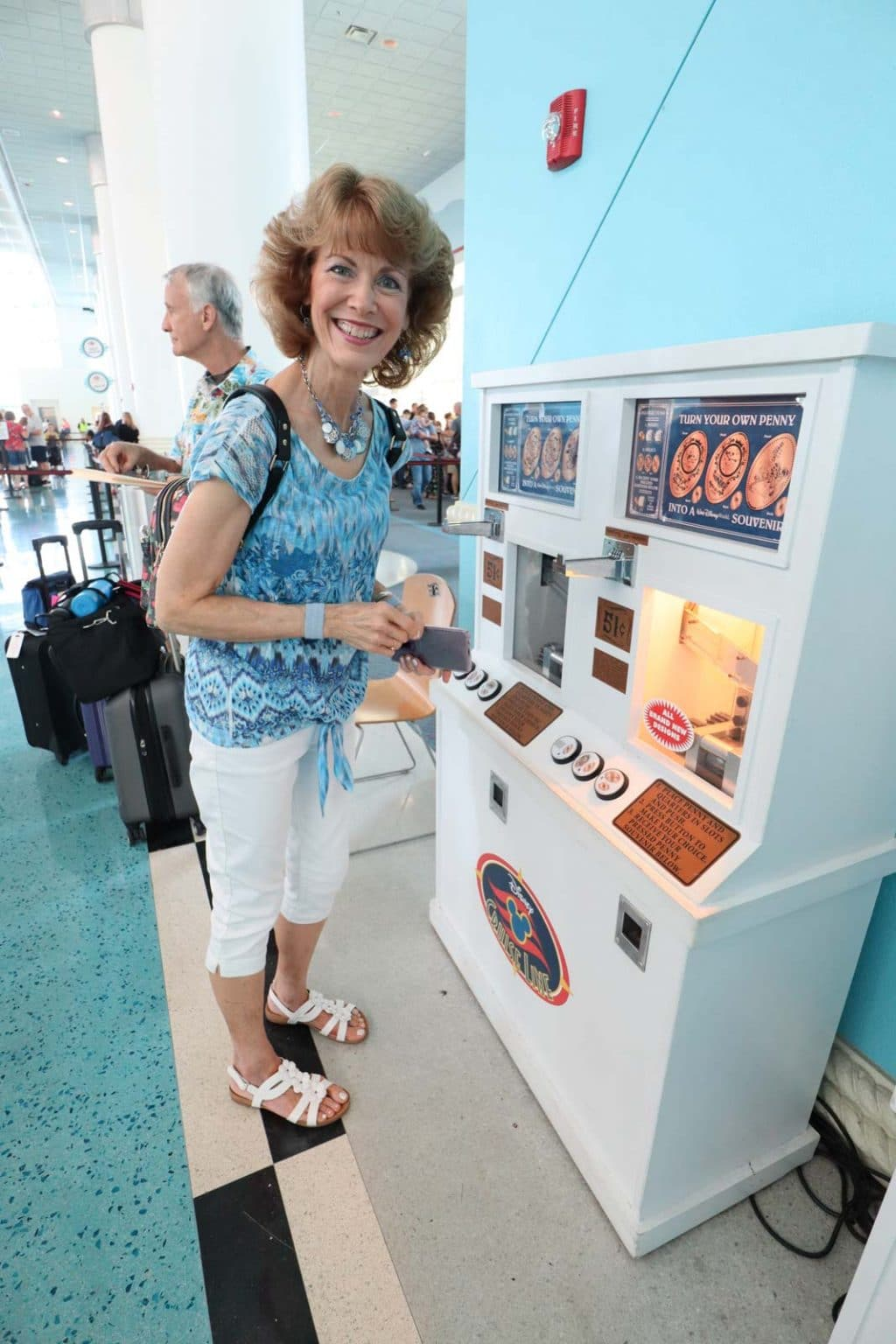 A woman using the pressed penny machine at the Port Canaveral cruise terminal.