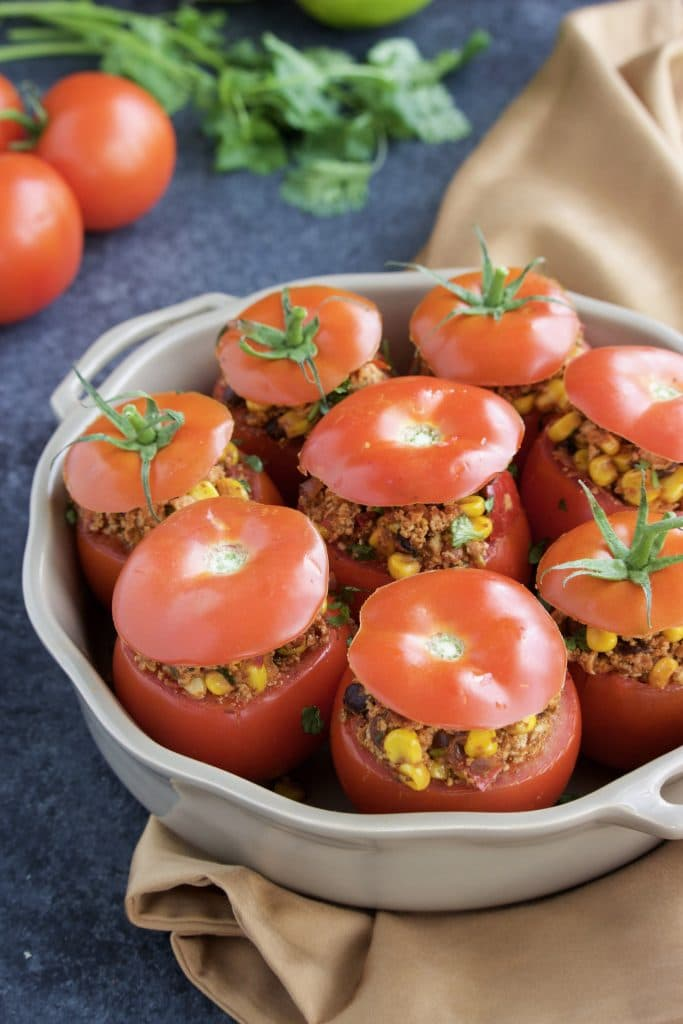 A casserole dish filled with stuffed tomatoes with the tops put back on.