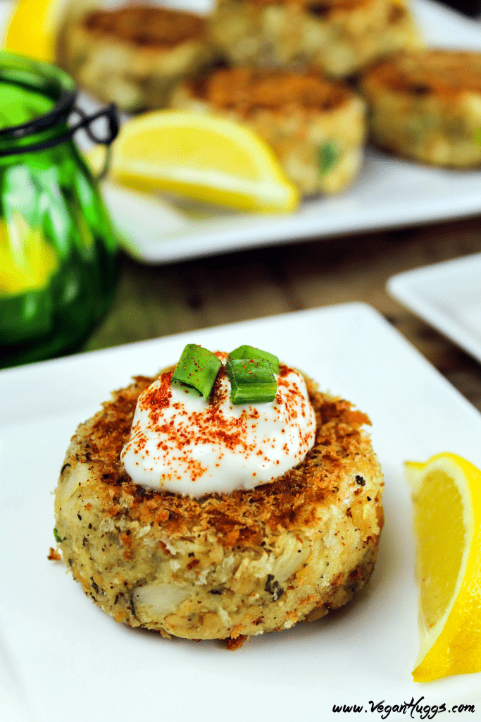 A vegan crab cake topped with sauce and green onions on a square white plate.