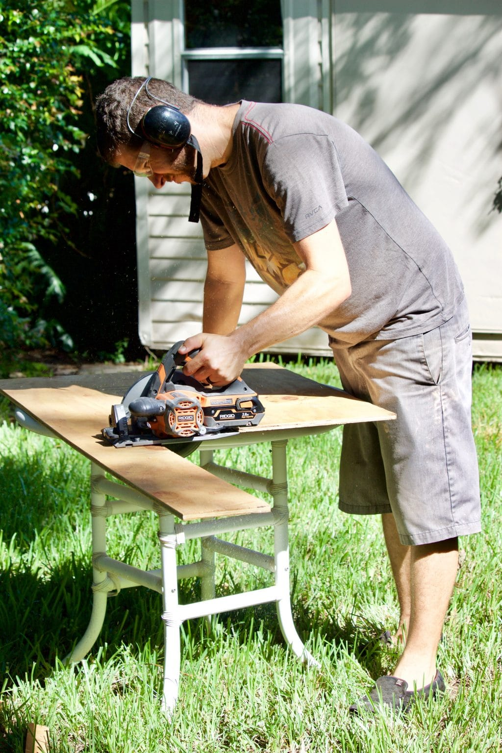 A man with a table saw cutting a piece of plywood on a table over grass.