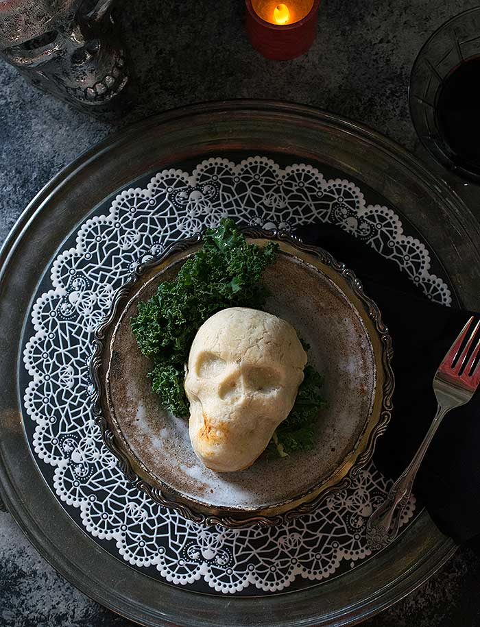 An edible skull on top of a dark plate and matching charger with a fork and a candle.
