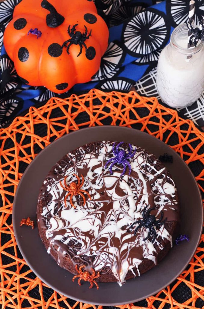 A vegan chocolate cake with a frosting spider wed and fake spiders on a colorful background.