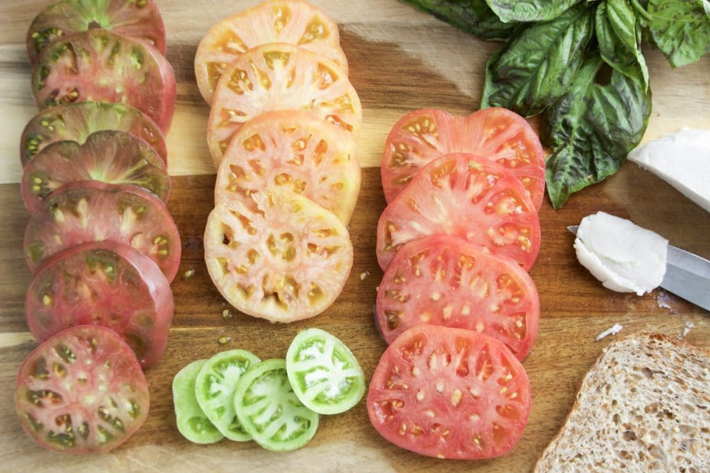 Multiple slices of heirloom tomatoes and basil on a cutting board.