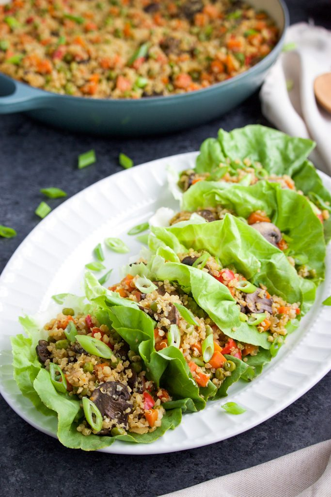 Lettuce wraps filled with quinoa and vegetables on a large white platter next to full pan.