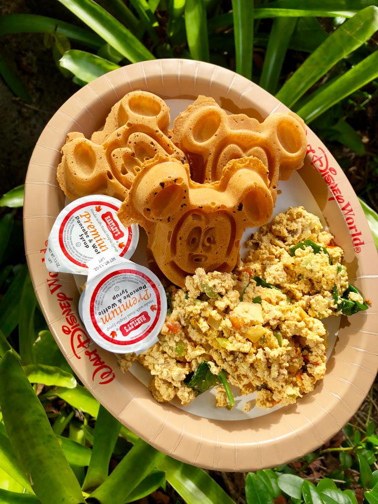 Vegan Mickey waffles with maple syrup and a tofu scramble on a Walt Disney World brown paper plate over green bushes.