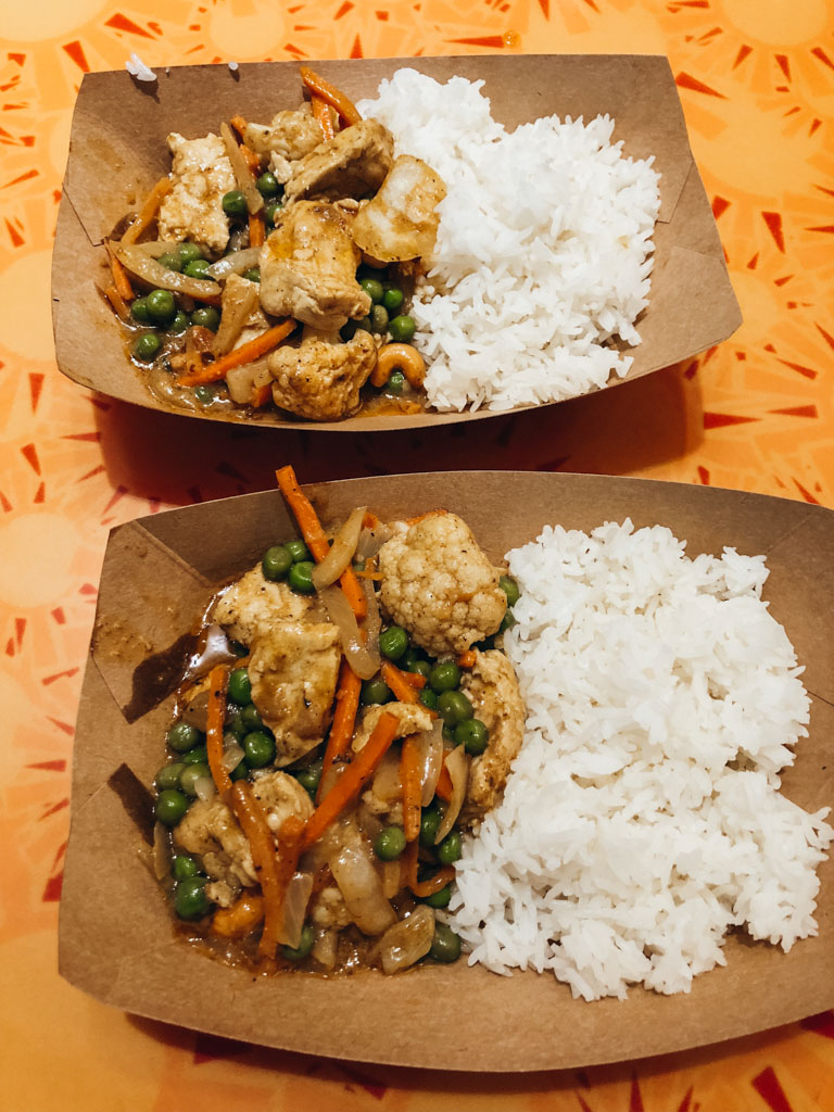 Two brown paper bowls that are filled with white rice and vegan korma on an orange table.