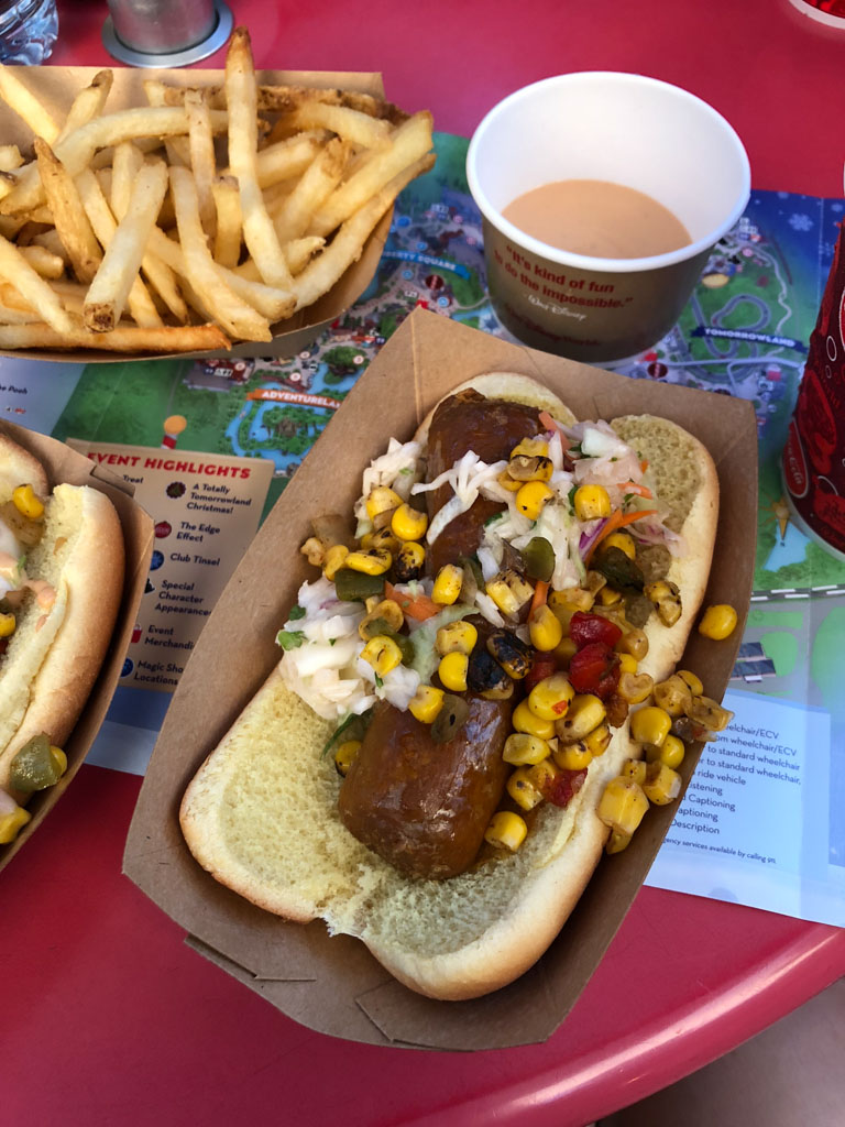 Vegan Beyond sausage hot dogs with corn salsa and French fries in brown paper cups sitting on a red table.