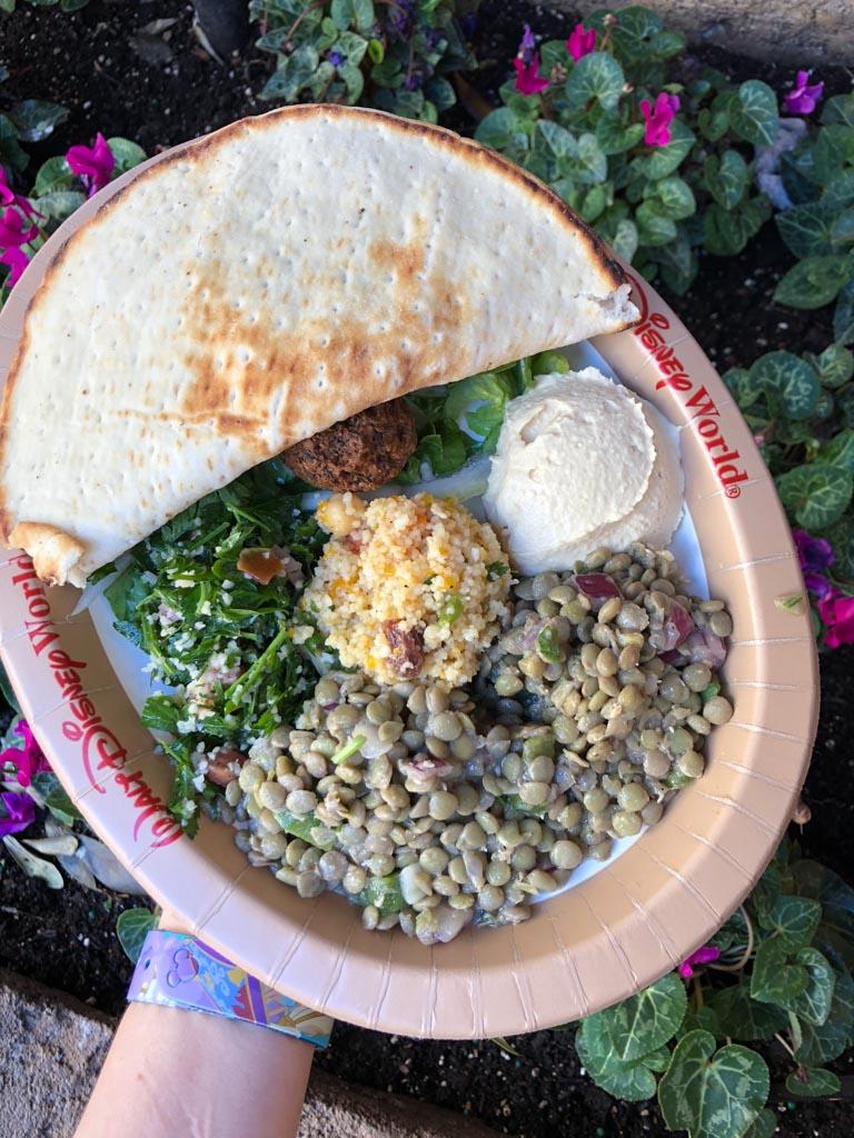A Walt Disney World paper plate filled with vegan falafel, pita, lentil salad, tabouleh, and hummus over pink flowers.