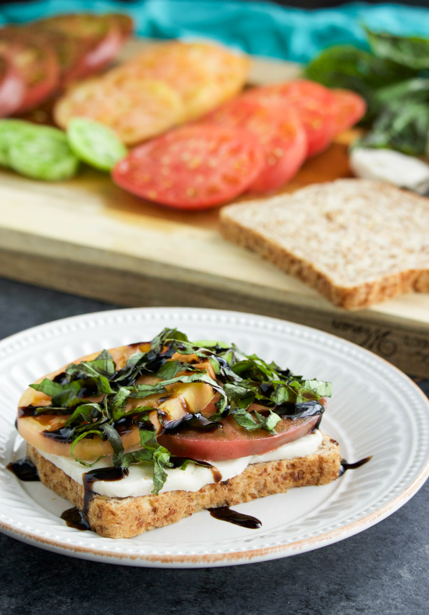 A caprese sandwich being assembled on a white plate next to a cutting board with sandwich ingredients on it.