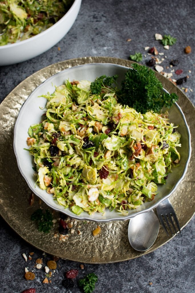 A large bowl filled with brussel sprout salad on a metallic plate on a dark textured background.