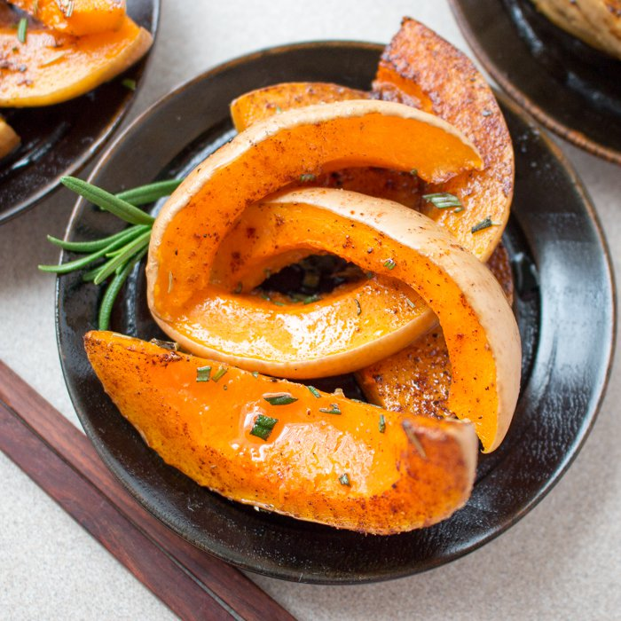 Large slices of roasted butternut squash own a black plate with fresh rosemary.