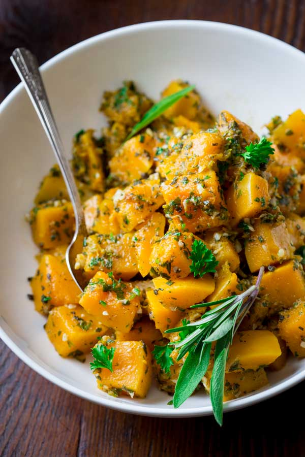 A large white bowl filled with garlic herb butternut squash and a metal spoon with fresh herbs.