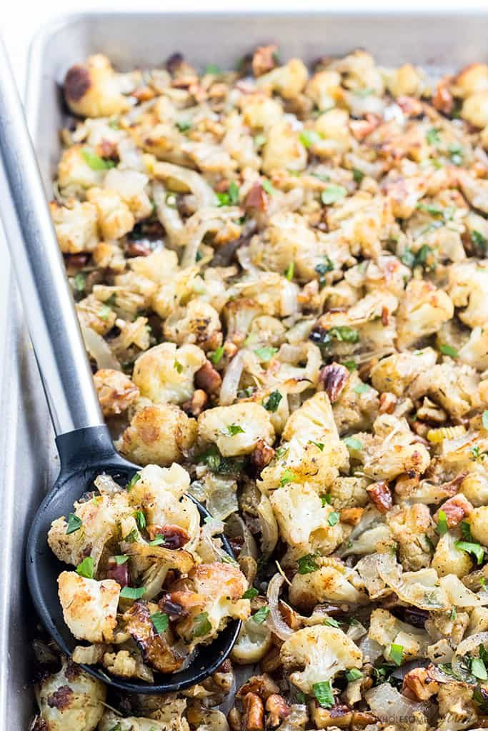 A large pan filled with low-carb cauliflower stuffing with a big spoon.