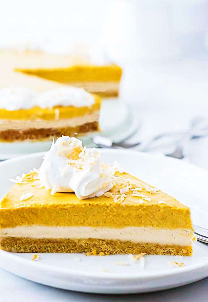 A slice of 3-layer vegan pumpkin cheesecake with whipped cream on a white plate.