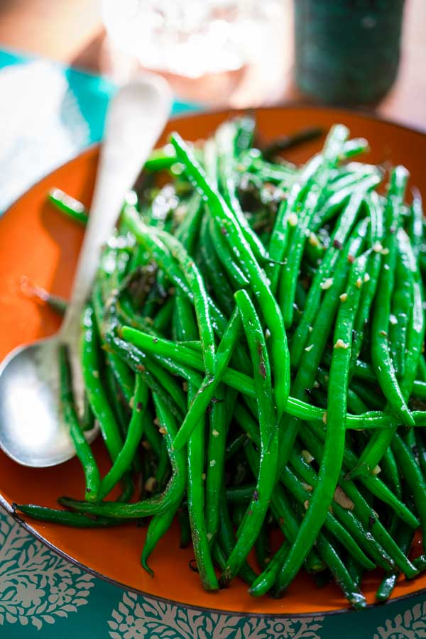 A large plate filled wit skillet green beans and a large metal spoon.