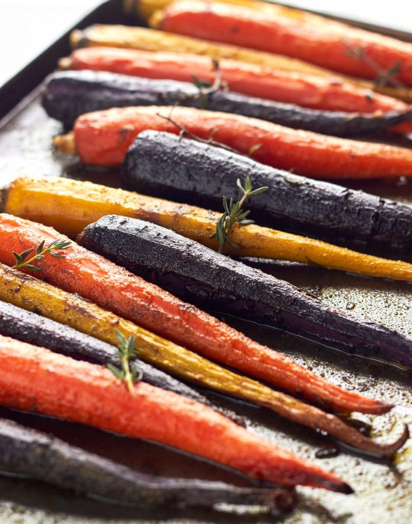 Large roasted rainbow carrots on a baking tray with fresh herbs.