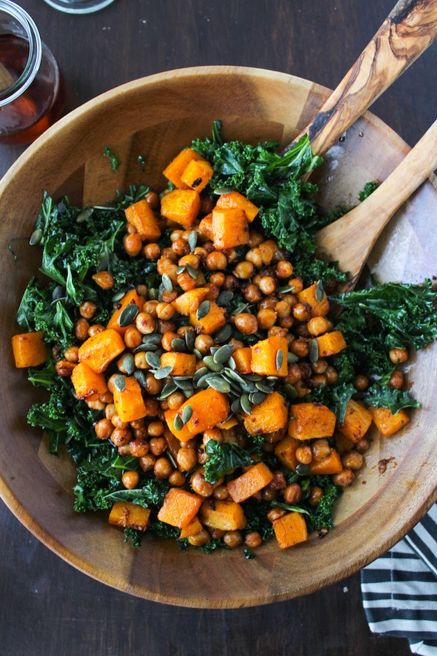 A wooden bowl filled with kale butternut squash salad on a rustic background.