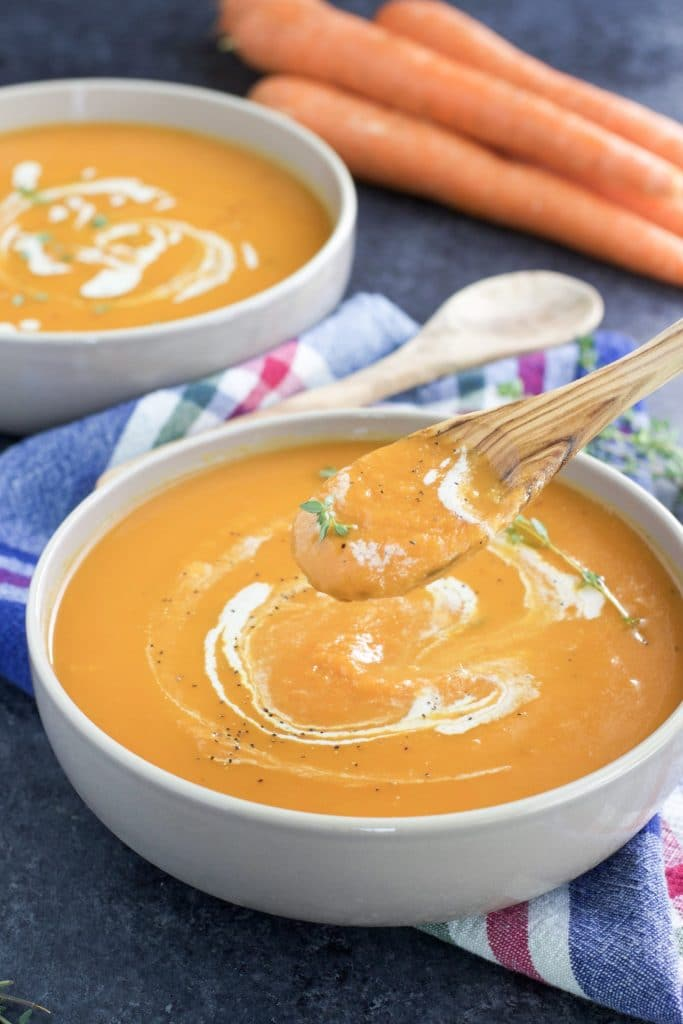 A wooden spoon dipping into a white bowl filled with vegan carrot soup next to another bowl of soup and some carrots.