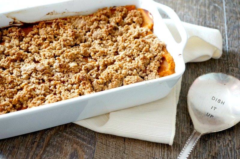 """A white baking dish of vegan sweet potato casserole next to a white napkin and a spoon that says, """"dish it up."""""""