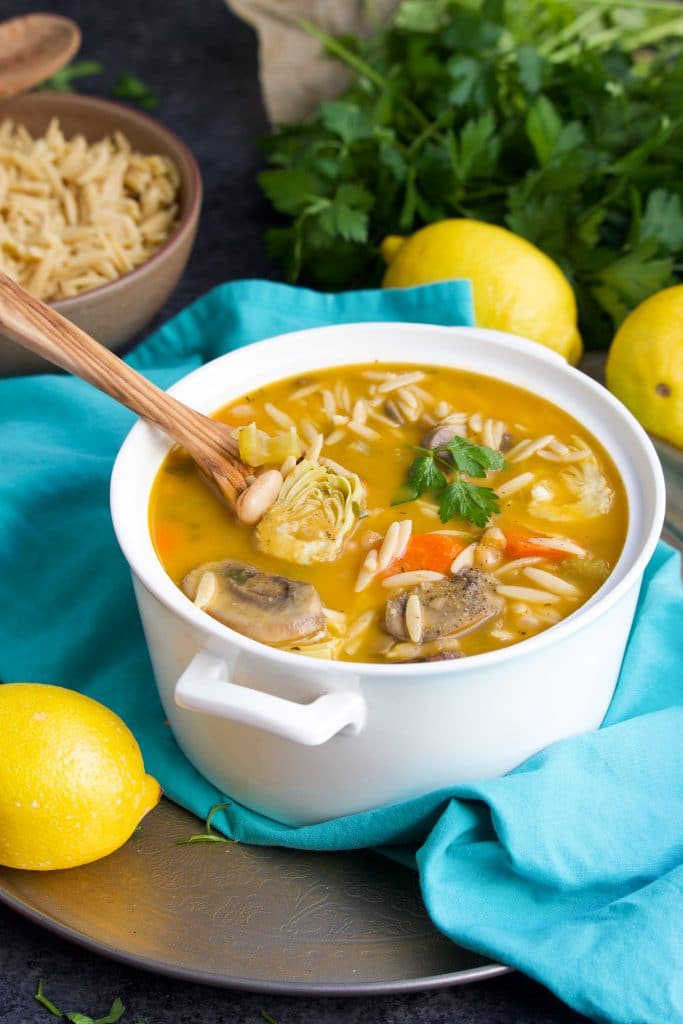 A white pot filled with soup and a wooden spoon on top of a teal napkin next to lemons and a bowl of orzo and parsley.