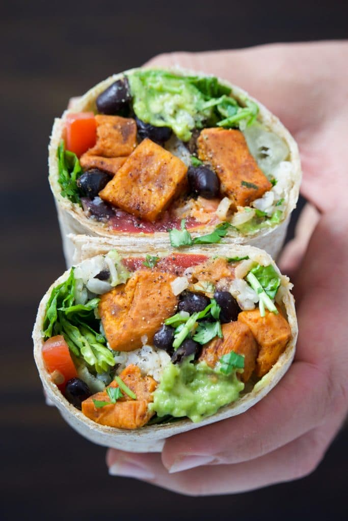 A hand holding a vegan burrito cut in half and stacked on top of each other.