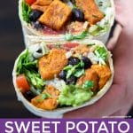 A hand holding a sweet potato black bean burrito cut in half.
