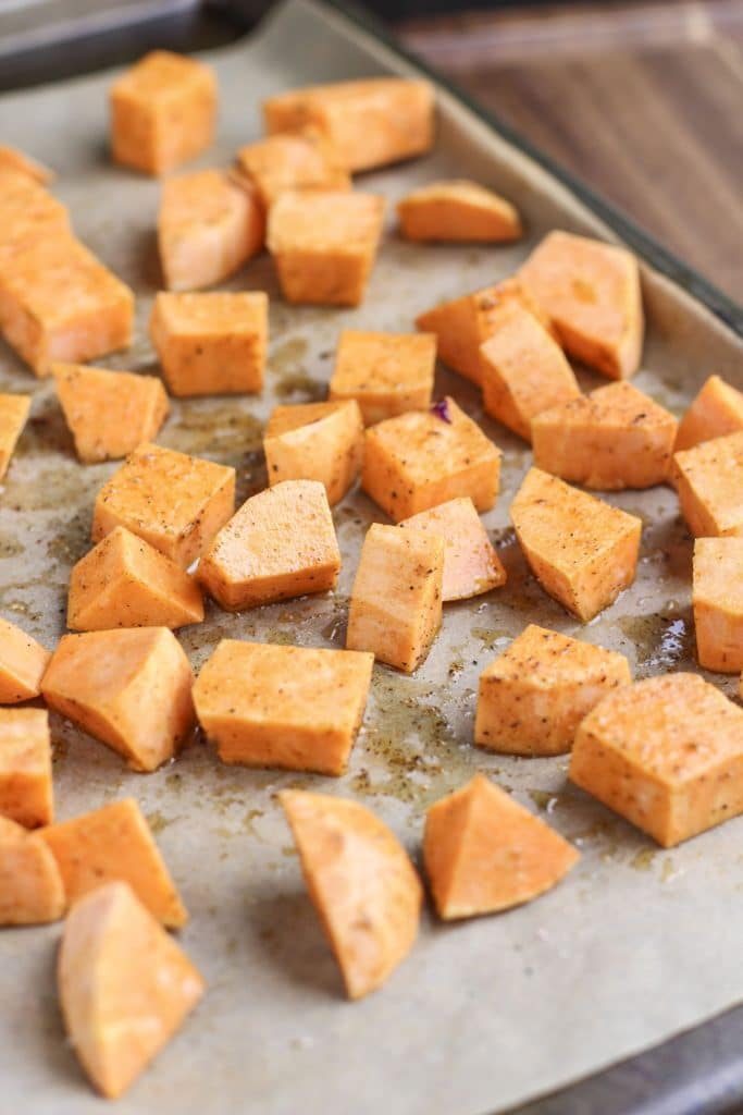 A baking tray lined with parchment paper and filled with sweet potato chunks on a rustic background.