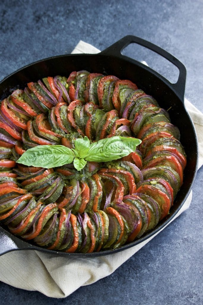 Low-carb thinly sliced zucchini, tomatoes, and red onions arranged in a circular pattern inside a cast iron pan on a textured blue background.