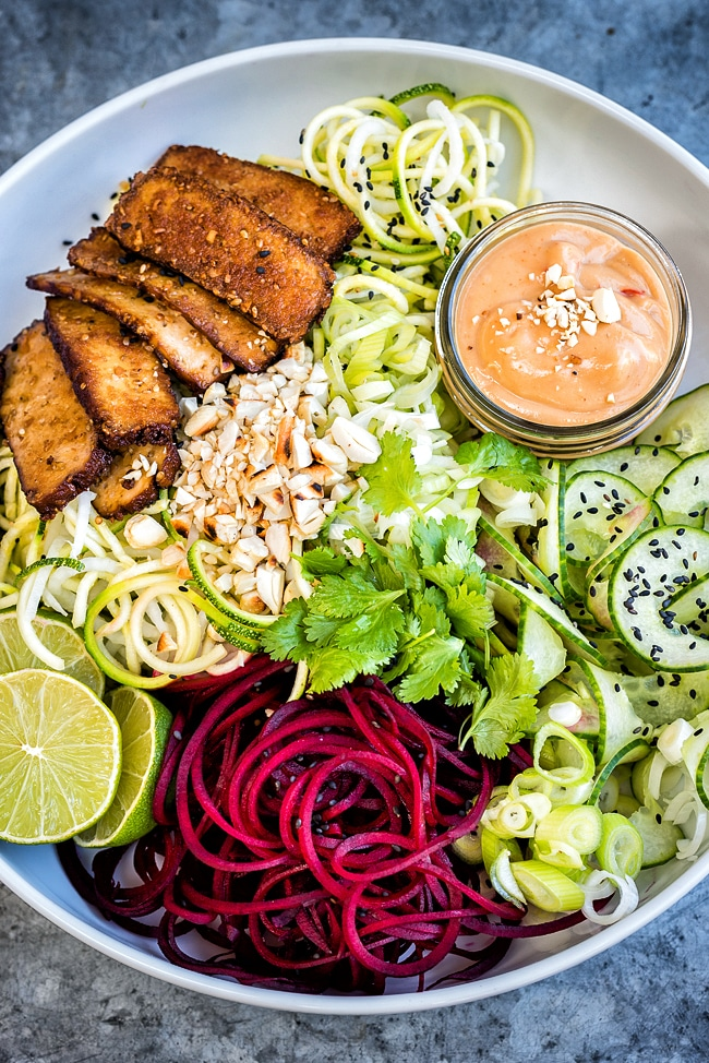 A low-carb vegan bowl of spiraled zucchini noodles with spicy tofu and peanut sauce on a textured background.