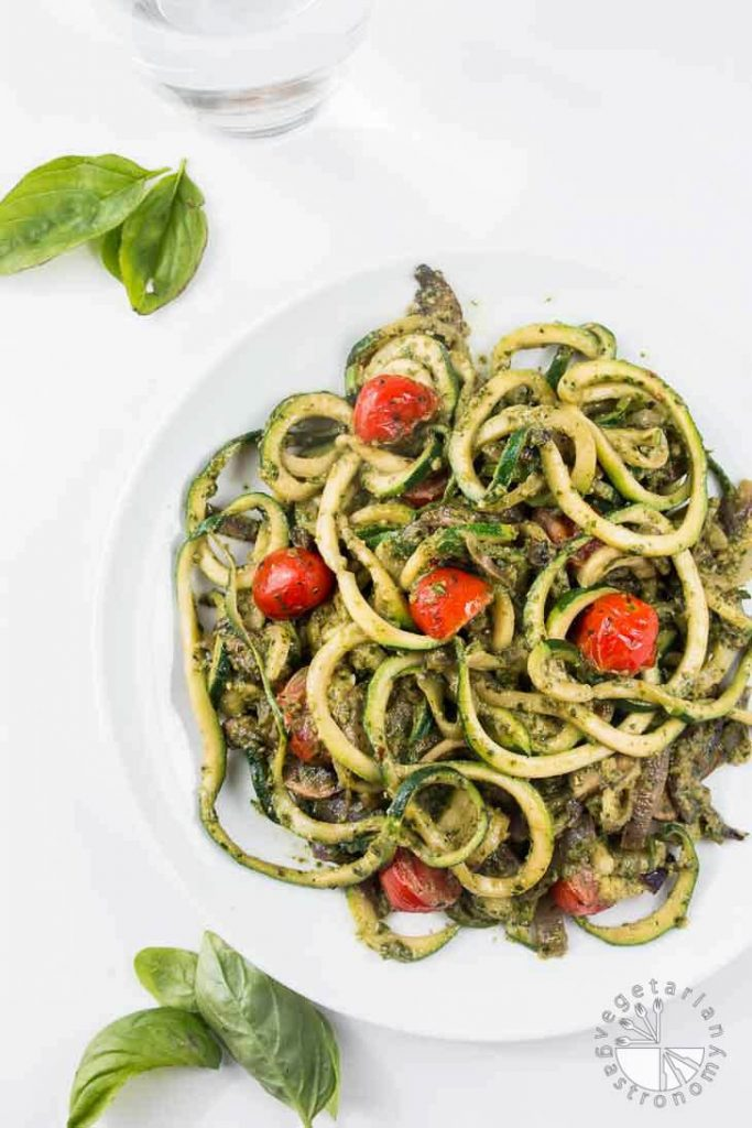 Low-carb vegan pesto zucchini noodles in a white bowl on a white background.