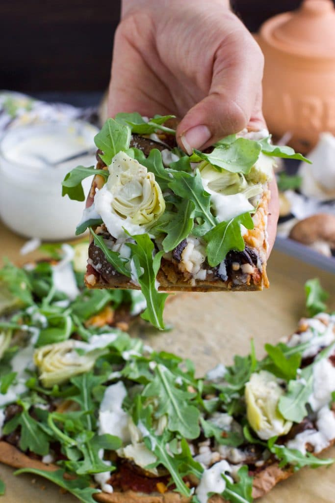 A hand holding a piece of flatbread pizza with artichokes and arugula.