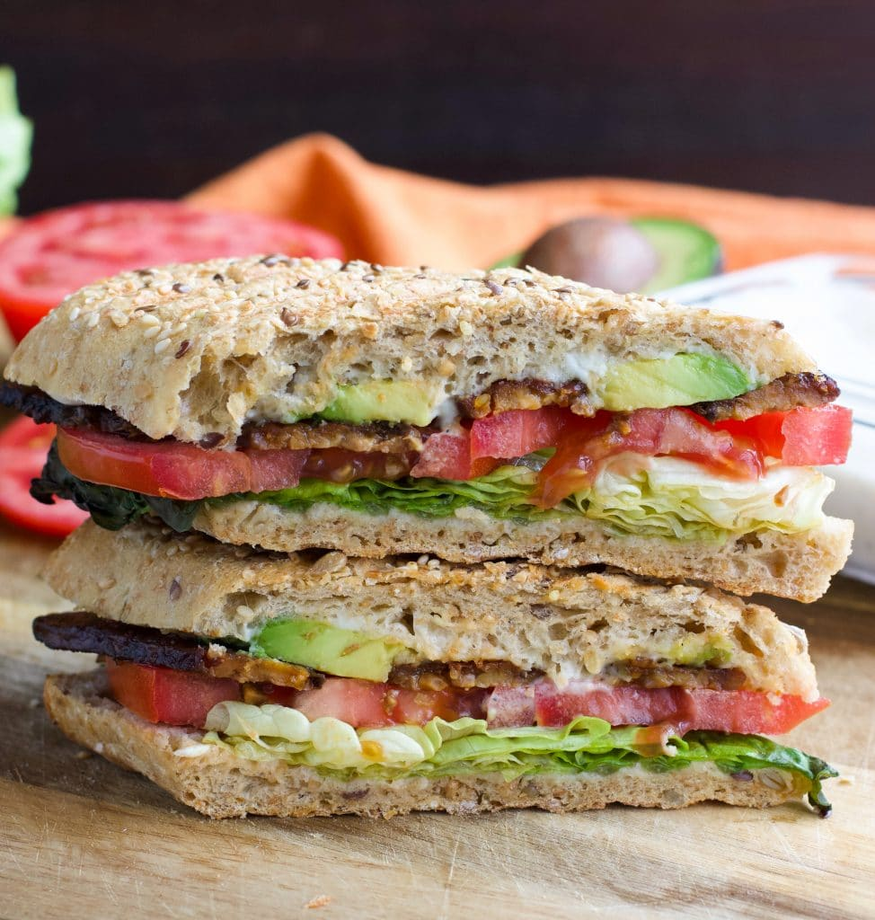 Two halves of a TTLA Whole Foods vegan sandwich stacked on top of each other on a rustic background.