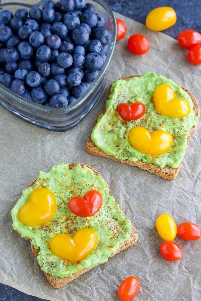 Two slices of toast next to a container of blueberries on a piece of parchment paper.