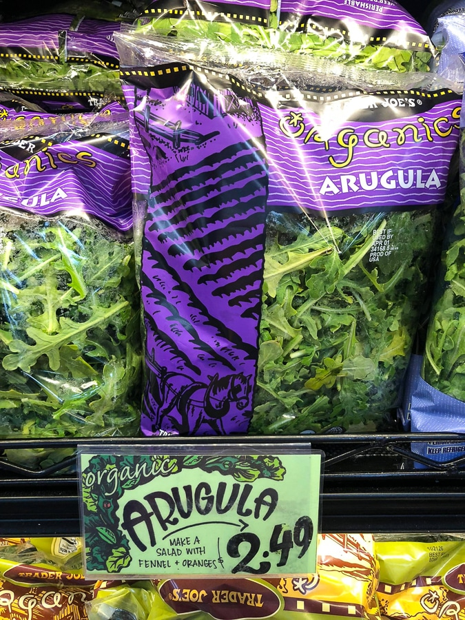 Multiple bags or organic arugula on a shelf at Trader Joe's.