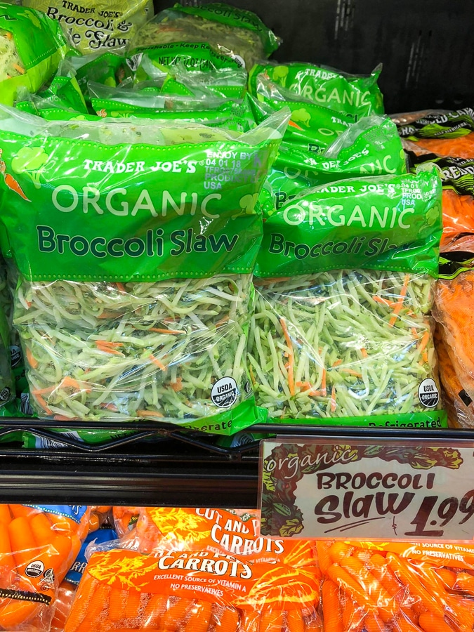 Multiple bags of organic broccoli slaw on a shelf at Trader Joe's.