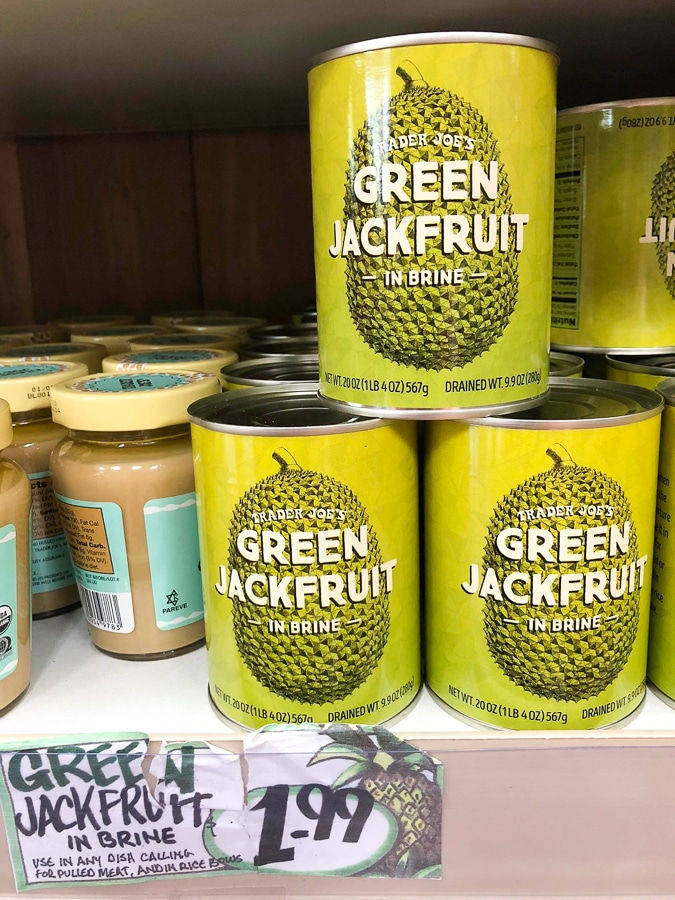 Cans of green jackfruit for $1.99 each on a shelf at Trader Joe's.