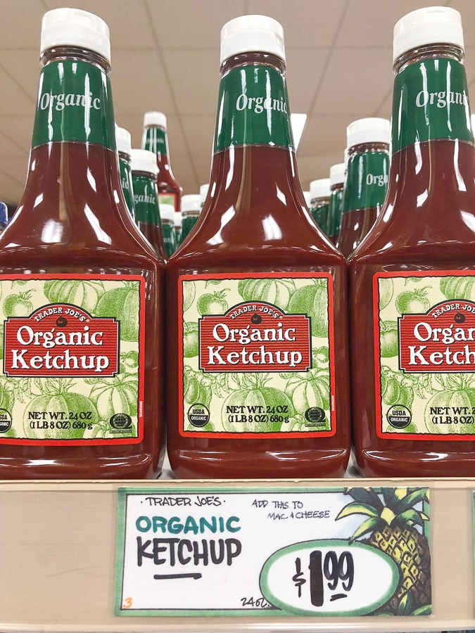 Bottles of organic ketchup on a shelf at Trader Joe's.