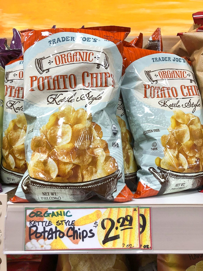 Bags of organic kettle style potato chips on a shelf at Trader Joe's.