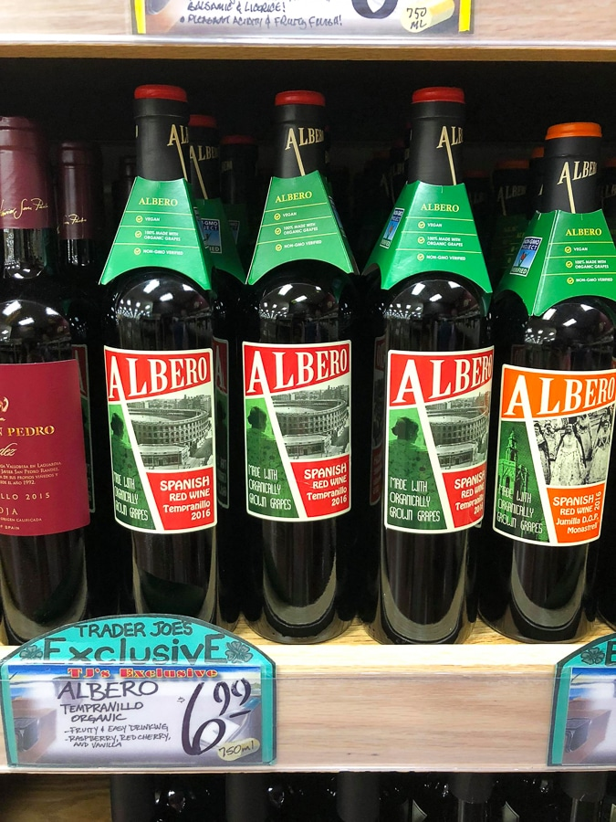 Multiple glass bottles of organic vegan wine on a shelf at Trader Joe's.