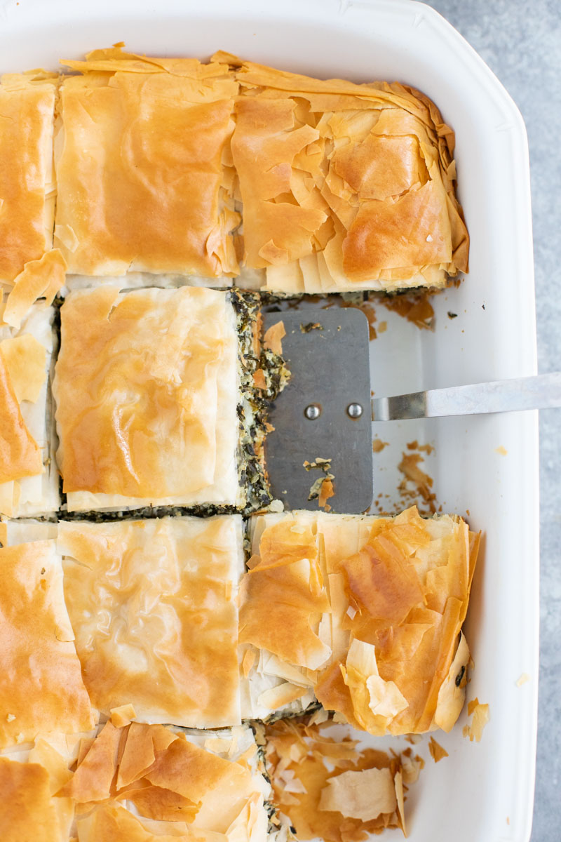 A white casserole dish filled with vegan spanakopita and a spatula.