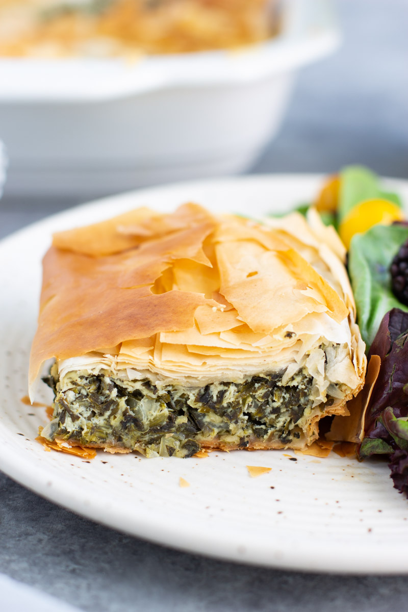 A piece of spinach pie on a white plate with a salad on a gray background.