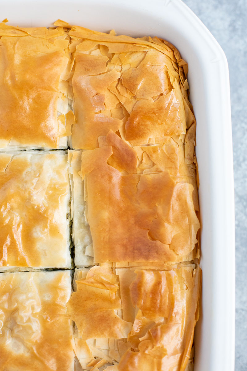 A close up view of the spinach pie cut into squares with crispy filo topping in a white casserole dish.