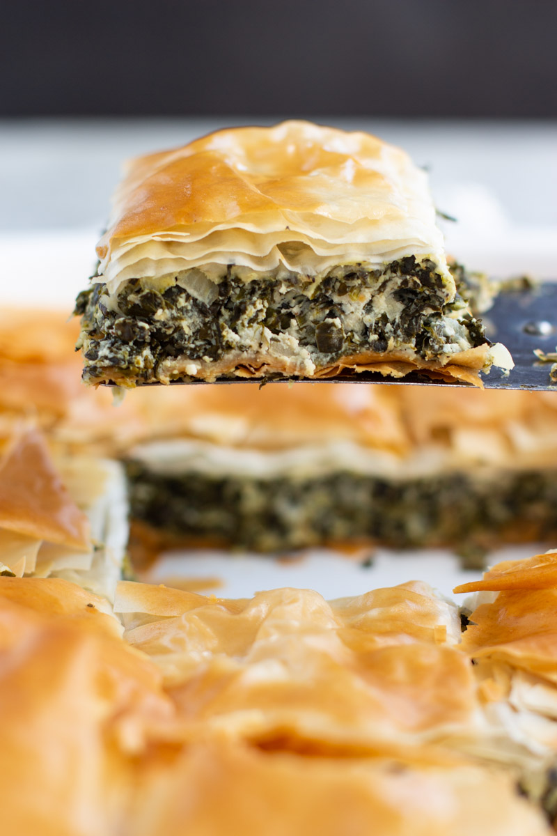 A spatula holding a slice of vegan spanakopita over the rest of the pie.